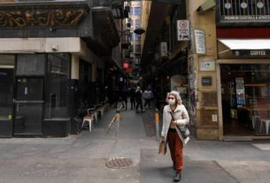 A woman wearing a face mask to help curb the spread of the coronavirus walks in Centre Place in Melbourne, Australia (Photo: AP)